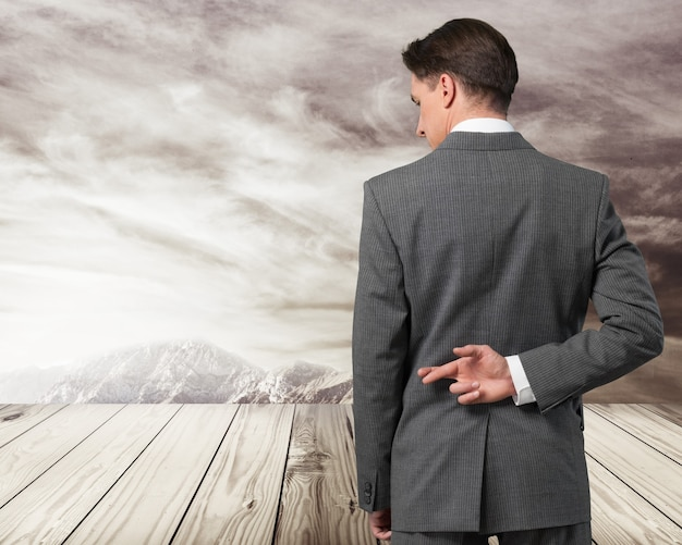 背中の後ろで指を交差させたビジネスマン-幸運や不誠実の概念