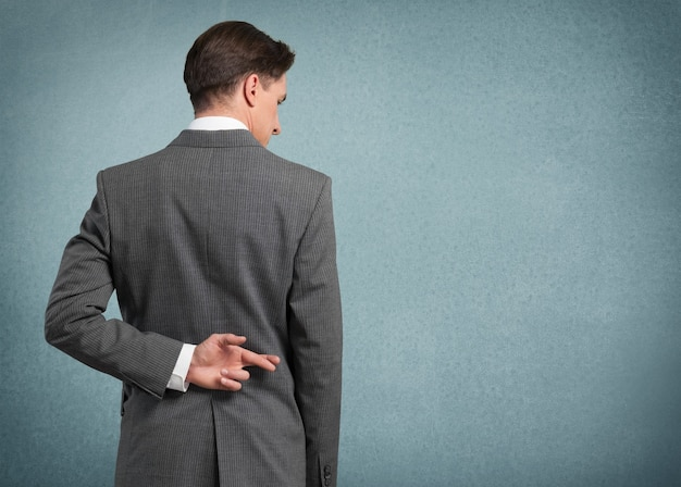 Бизнесмен, скрестив пальцы за спиной - концепция на удачу или бесчестие