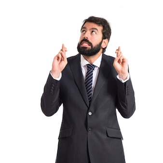 Businessman with his fingers crossing over white background