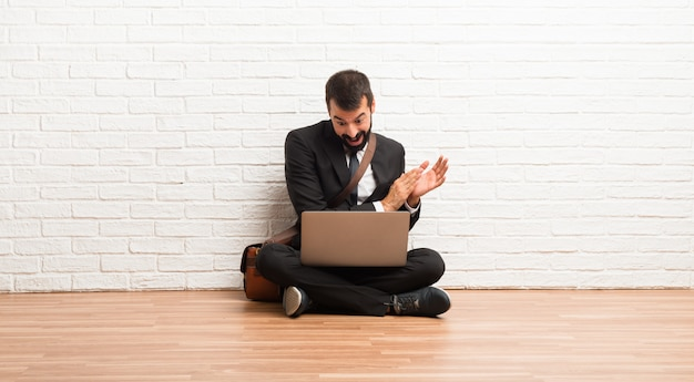 Businessman with his laptop sitting on the floor applauding after presentation in a conference