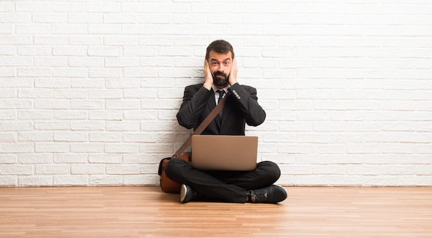 Businessman with his laptop sitting on the floor covering both ears with hands