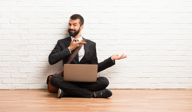 Businessman with his laptop sitting on the floor extending hands to the side for inviting to come