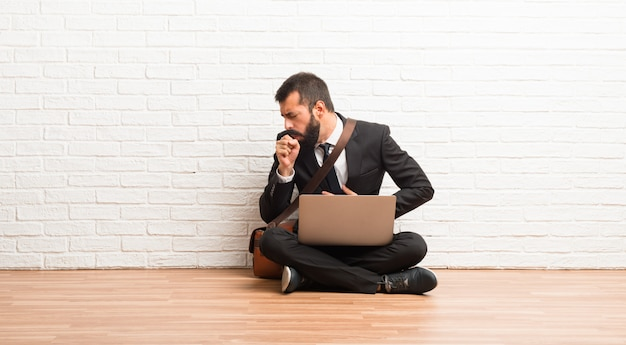 Businessman with his laptop sitting on the floor is suffering with cough and feeling bad