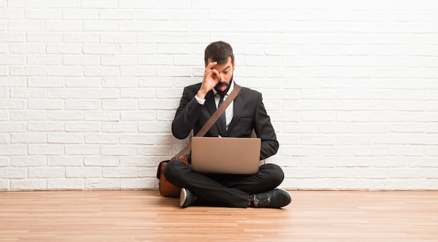 Businessman with his laptop sitting on the floor makes funny and crazy face emotion