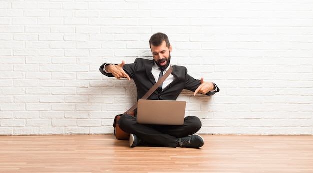 Businessman with his laptop sitting on the floor pointing with finger at someone and laughing a lot