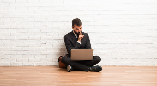 Businessman with his laptop sitting on the floor showing a sign of closing mouth and silence gesture