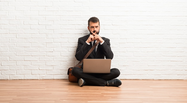 Businessman with his laptop sitting on the floor showing a sign of silence gesture