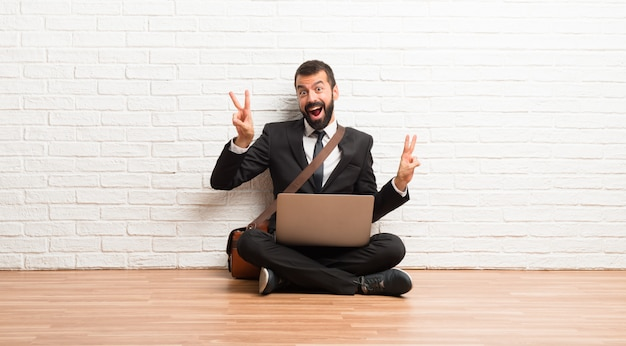 Businessman with his laptop sitting on the floor smiling and showing victory sign with both hands
