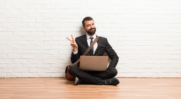 Businessman with his laptop sitting on the floor smiling and showing victory sign with a cheerful face