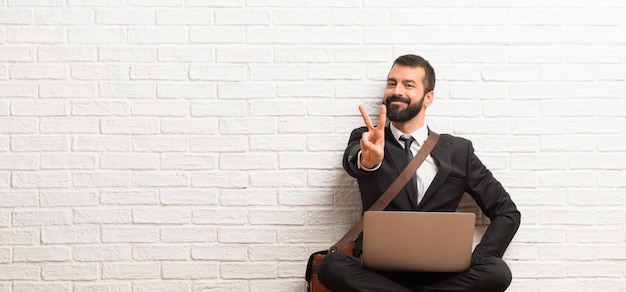 Businessman with his laptop sitting on the floor smiling and showing victory sign