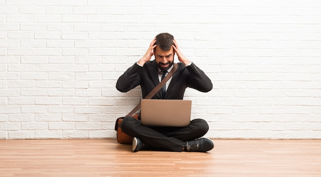 Businessman with his laptop sitting on the floor takes hands on head because has migraine