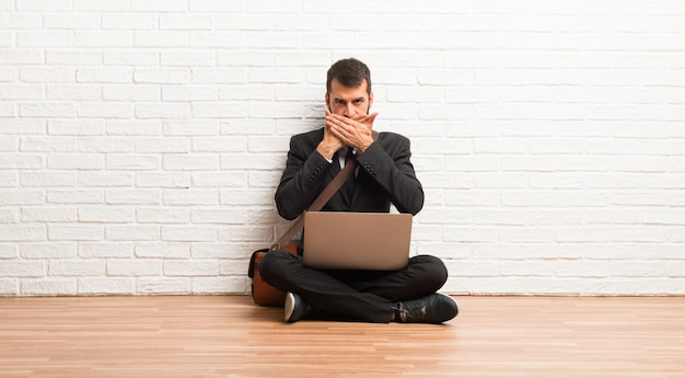 부적절 한 무언가를 말하기 위해 손으로 입을 덮고 바닥에 앉아 자신의 노트북과 사업가