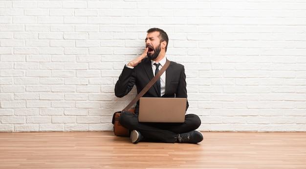 あくびと手で広い口を覆って床に座って彼のラップトップを持ったビジネスマン