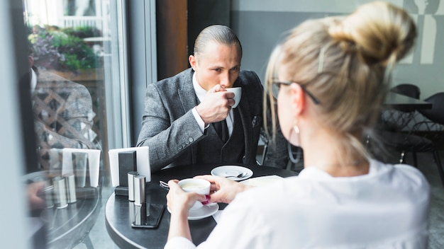 レストランでコーヒーを飲む彼のパートナーとのビジネスマン