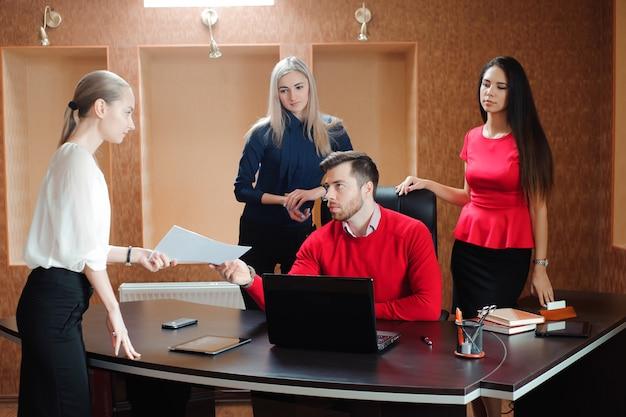 彼のスタッフ、屋内で近代的な明るいオフィスでバックグラウンドで人々のグループを持ったビジネスマン