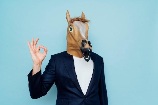 馬マスクを持つビジネスマン