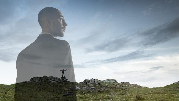 背景、二重露光の風景を持つビジネスマン。