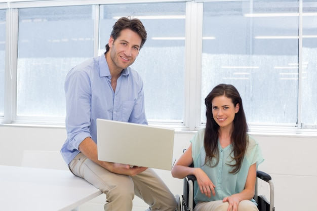 Businessman with laptop and businesswoman in wheelchair