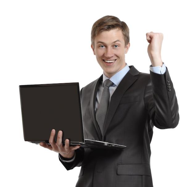 くいしばられた握りこぶしで勝利を祝って手を上げたラップトップを持つビジネスマン。孤立