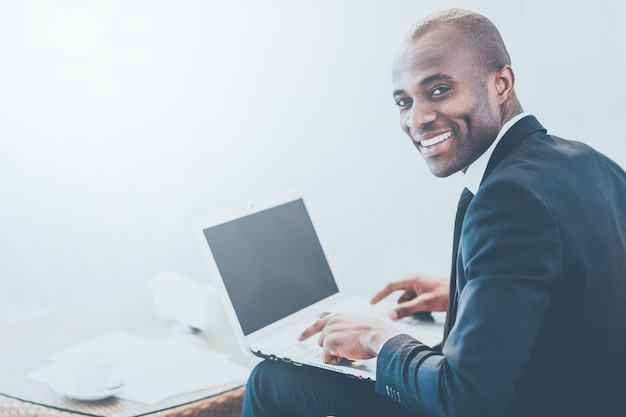 Бизнесмен с ноутбуком. веселый молодой африканский бизнесмен печатает что-то на ноутбуке и смотрит через плечо