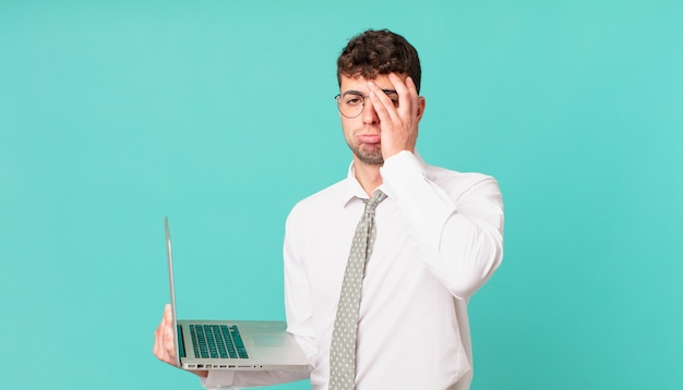 Бизнесмен с ноутбуком, чувствуя скуку, разочарование и сонливость после утомительной, скучной и утомительной задачи, держа лицо рукой