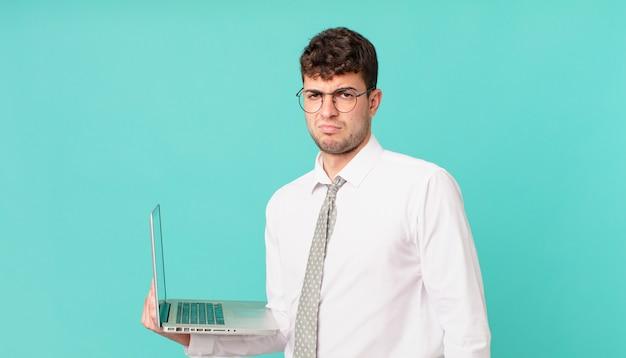 悲しみ、動揺、または怒りを感じ、否定的な態度で横を向いて、意見の相違に眉をひそめているラップトップを持つビジネスマン