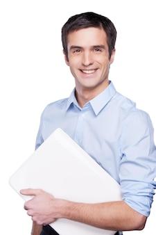 Бизнесмен с ноутбуком. красивый молодой человек в синей рубашке держит ноутбук и улыбается, стоя изолированным на белом