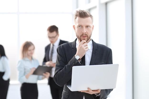 사무실 로비의 배경에 노트북과 사업가. 사람과 기술