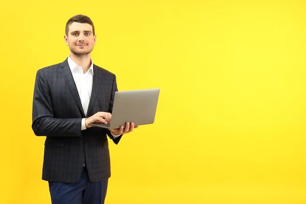 Бизнесмен с ноутбуком на желтом фоне, место для текста.