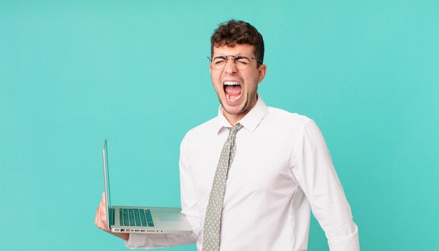 Businessman with laptop shouting aggressively, looking very angry, frustrated, outraged or annoyed, screaming no