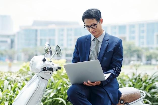 バイクに座っているラップトップを持ったビジネスマン