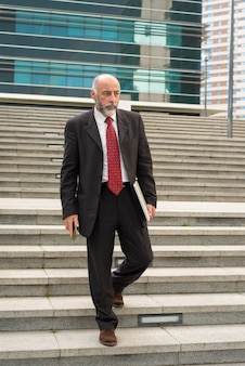 Businessman with laptop and smartphone walking on steps