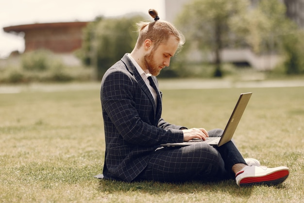 Businessman with laptop in a summer city