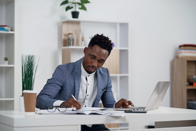 Businessman with laptop. young african businessman is typing something on laptop in his office.