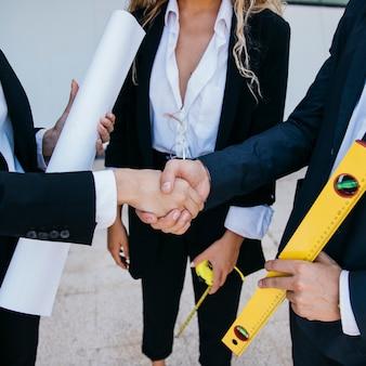 Бизнесмен с уровнем и бизнесмен, рукопожатие