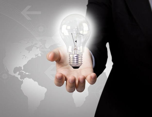 Businessman with light bulb and map background
