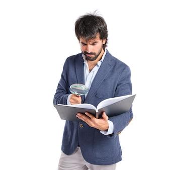 Uomo d'affari con lente di ingrandimento che reding un libro sopra priorità bassa bianca