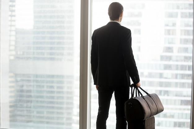 Businessman with luggage standing in front of large window.