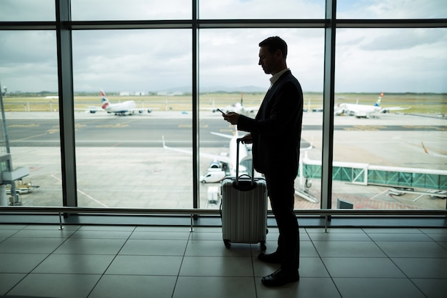 Businessman with luggage using mobile phone