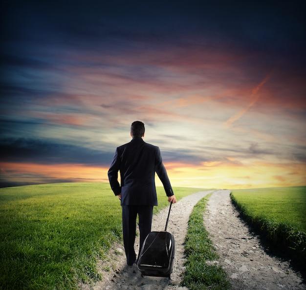 Бизнесмен с багажом гуляет по дороге в сельской местности с зеленой травой на закате
