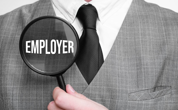 Businessman with magnifying glass on the white background. employer sign