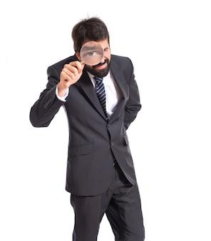 Uomo d'affari con lente di ingrandimento su sfondo bianco