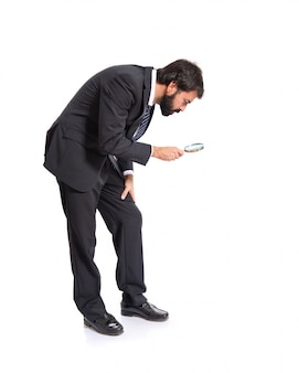 Businessman with magnifying glass over white background