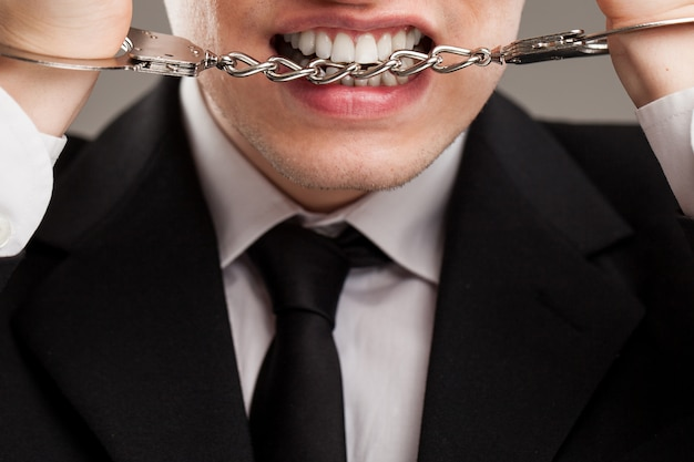 Businessman with manacles on his hands
