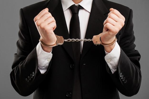 彼の手に手錠を持ったビジネスマン