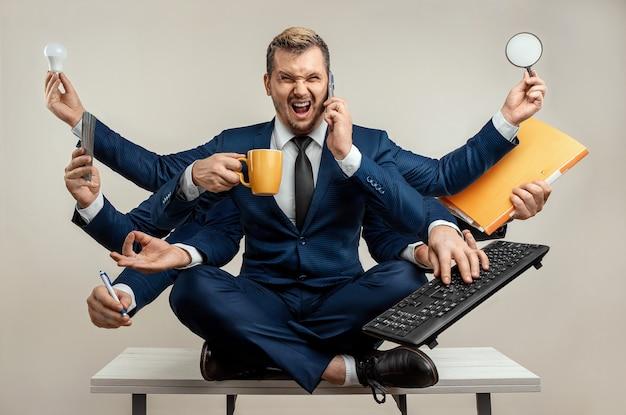スーツを着た多くの手を持つビジネスマンは、複数のオブジェクトと同時に動作します