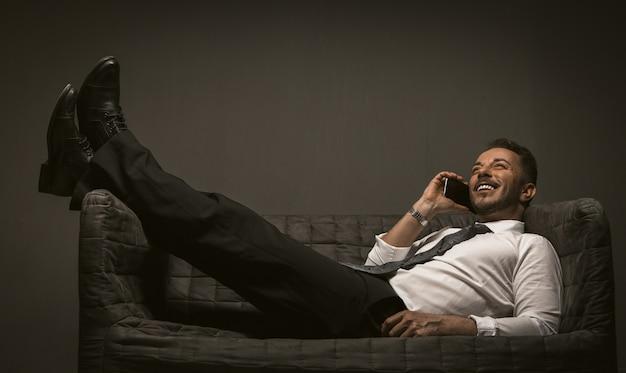 携帯電話を持ったビジネスマンがソファに足を投げてあります。灰色の背中にスマートフォンであぐらをかいてソファで横になっている笑みを浮かべて男。