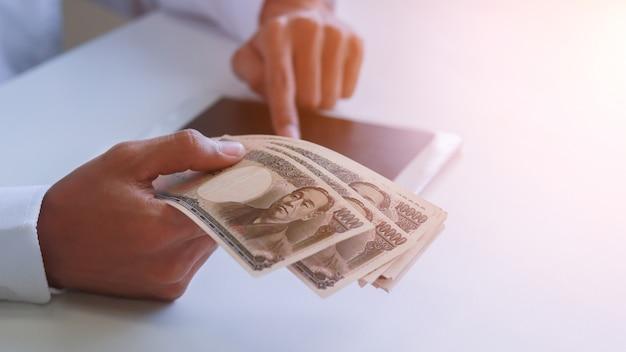 손에 돈, 엔, 투자, 성공 및 수익성 사업 개념으로 사업가.