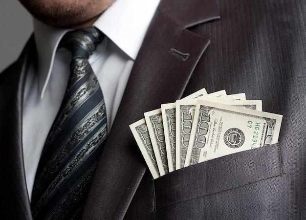 Бизнесмен с деньгами в кармане костюма