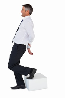Businessman with one foot on cube and hands behind his back